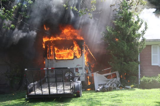 A recreational vehicle parked between two houses on Apple Valley Drive in Middletown spreads a fire at one house to the house next door.