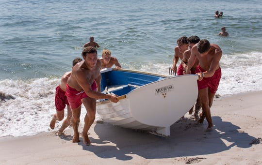 Ortley guards help put their lifeguard boat back up near the lifeguard stand after some used it for a morning workout on July 21, 2019.