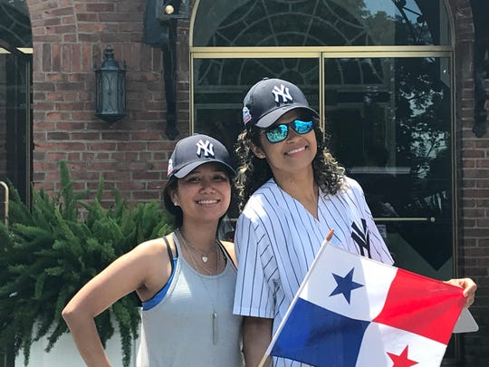 Panama natives Karen Cortes, left, and Nilsya Villarrel stand in front of the National Baseball Hall of Fame before the Induction of Mariano Rivera.