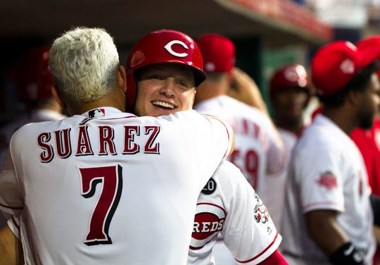 Cincinnati Reds left fielder Josh VanMeter (17) is embraced by Cincinnati Reds third baseman Eugenio Suarez (7) after hitting his first home run in the Major Leagues in the seventh inning of the MLB game between Cincinnati Reds and St. Louis Cardinals on Saturday, July 20, 2019, in Cincinnati.