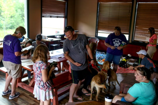 Families visiting and adopting new pets mingle together in the backroom that was provided due to the heat wave during an adoption event by Two Ladies Caring Dog Rescue at Ravenwood Coffee in Clarksville, Tenn., on Saturday, July 20, 2019.