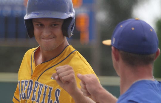 Martensdale-St. Marys sophomore Trey Baker bumps fists with coach Ethan Westphal at first base after getting a hit.