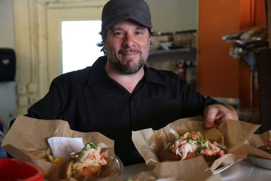 Proprietor Greg Mudge poses with a pair of lobster rolls at Mudgie's Deli in Detroit's Corktown neighborhood.