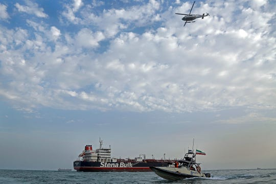 A speedboat and a helicopter of Iran's Revolutionary Guard move around a British-flagged oil tanker Stena Impero which was seized on Friday by the Guard, in the Iranian port of Bandar Abbas, Sunday.