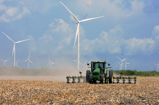 In this Aug. 17, 2015, file photo, a farmer plows his recently harvested field under wind turbines in the agricultural area north of Rio Hondo, Texas, near the New Mexico border.