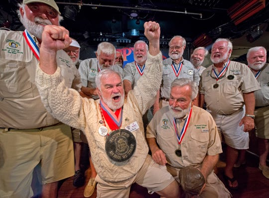 In this Saturday, July 20, 2019, photo provided by the Florida Keys News Bureau, Joe Maxey, second from left, celebrates his victory at the Hemingway Look-Alike Contest at Sloppy Joe's Bar in Key West, Fla.