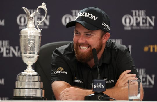 Shane Lowry smiles as he sits next to the Claret Jug trophy while he attends a press conference after he won the British Open.