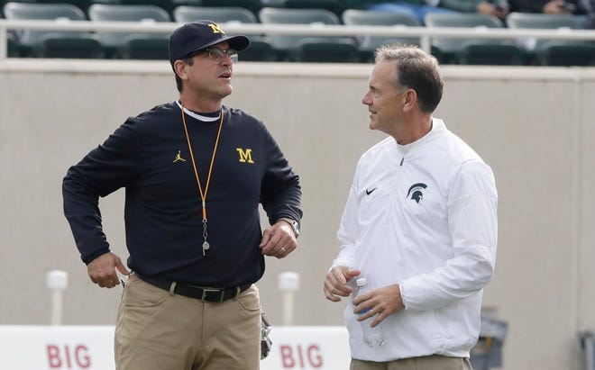 Michigan and coach Jim Harbaugh, left, are the preseason favorite to win the Big Ten, while Michigan State and coach Mark Dantonio were picked to finish third in the East.