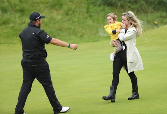 Shane Lowry goes to kiss his daughter Iris and hug his wife Wendy Honner on the 18th green after winning the British Open.