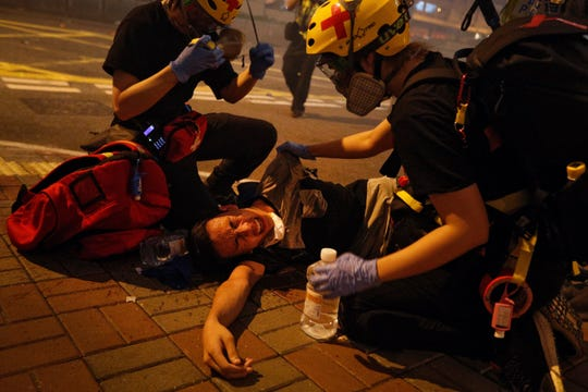 Medical workers help a protester in pain from tear gas fired by policemen on a street in Hong Kong, Sunday, July 21, 2019.