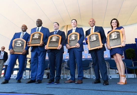 National Baseball Hall of Fame inductees Harold Baines, Lee Smith, Edgar Martinez, Mike Mussina, Mariano Rivera , and Brandy Halladay, widow of the late Roy Halladay, hold their plaques during Sunday's induction ceremony.