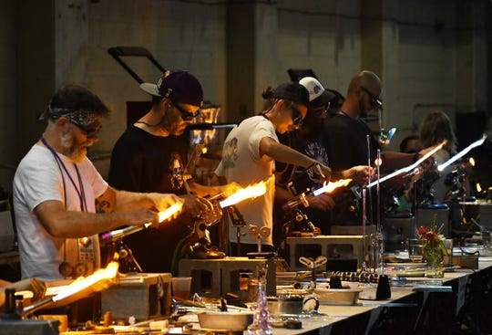 Glass artists work on their pieces during The Michigan Glass Project, a festival of glass, music and arts benefiting art programs in Detroit Public Schools at the Russell Industrial Center in Detroit, Michigan in this July 20, 2018, file photo.