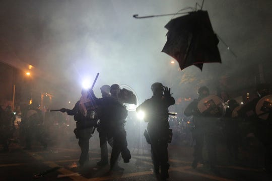 A broken umbrella flies by near riot police, during confrontation with protesters in Hong Kong Sunday, July 21, 2019.