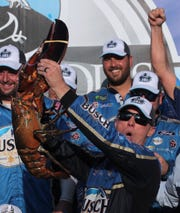 Kevin Harvick hoists a giant lobster in victory lane after winning a NASCAR Cup Series race at New Hampshire Motor Speedway on Sunday.