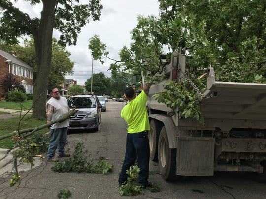 A work crew from the city of Dearborn removes tree branches from the 7800 block of Reuter late Sunday morning.