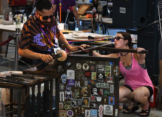 Artists Louie Sanchez and Rebecca Silverman work on a glass goblet that was auctioned at the 2018 Michigan Glass Project.