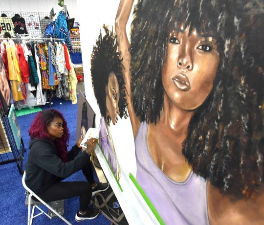 Artist Stina Aleah, of Elyria, paints a mural for DevaCurl, a hair care company in New York City, Sunday afternoon at Cobo Center.