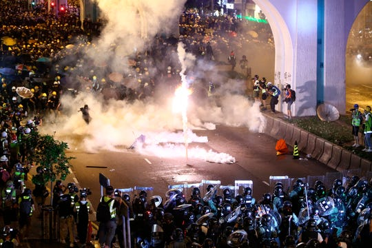 Protesters are engulfed by teargas during a confrontation with riot police in Hong Kong Sunday, July 21, 2019.