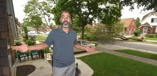 Area resident Mohamed Ali Sabra, of Dearborn, is thankful the tree that lies across Bertram fell into the street and not on homes.  (Todd McInturf, The Detroit News)