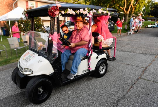 "With her father Glenn Schoenbaecler behind the wheel, Sarah Schoenbaecler, riding in a flamingo adorned golf cart, begins a ""Half Birthday/Christmas in July Parade"" through the Green Springs Subdivision decorated for Christmas in Newburgh Saturday. In addition to her flamingo adorned golf cart the parade featured firetrucks, units from the Hadi Shriners and mounted police, July 20, 2019."