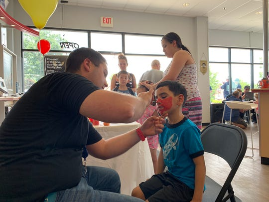 Yeray Ribera, who's heading into first grade this fall, gets his face painted at the eighth annual School Rocks Backpack Giveaway at the Verizon Wireless store on Lexington Road.