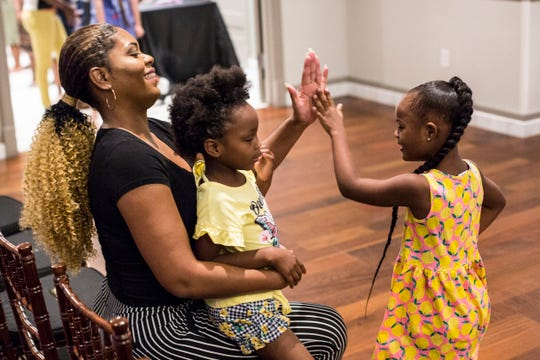 """Renadda Wiggins, left, high fives London Singleton, 6, during a practice walk before the Art of the Runway """"Rocking My Extra Chromosome Fashion Show"""" Sunday night at NOAH'S Event Venue, July 21, 2019. Wiggins, the founder of the fashion show, began The Art of Runway as a modeling agency for people with Down syndrome."""