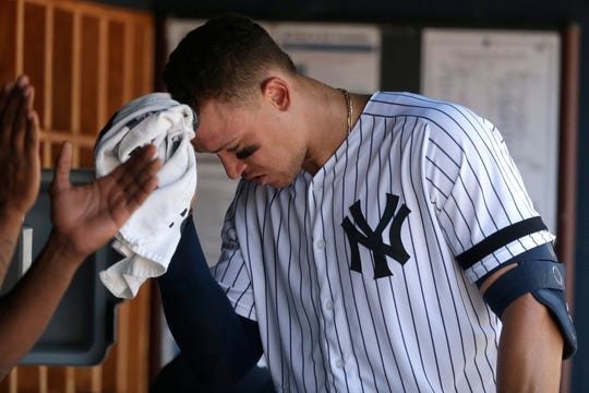 New York Yankees' Aaron Judge wipes away sweat during the third inning of a baseball game against the Colorado Rockies at Yankee Stadium, Sunday, July 21, 2019, in New York. (AP Photo/Seth Wenig)