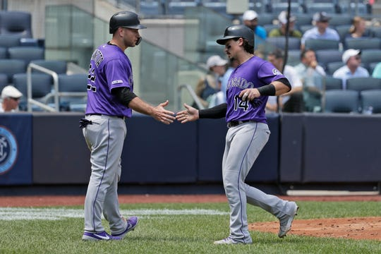 Colorado Rockies' Tony Wolters, right, and Chris Iannetta celebrate after scoring on a double hit by Nolan Arenado during the third inning of a baseball game against the New York Yankees at Yankee Stadium, Sunday, July 21, 2019, in New York. (AP Photo/Seth Wenig)