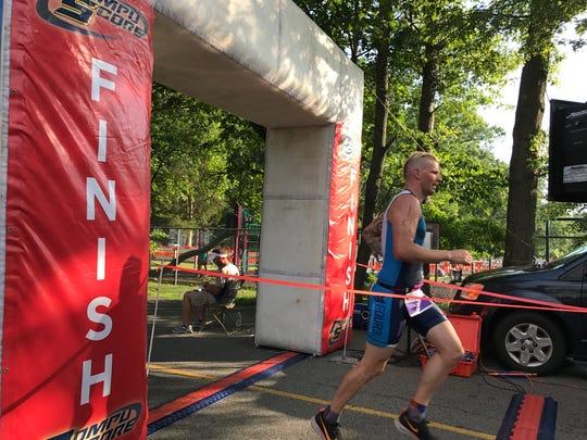 Jeffrey Melgaard crosses the finish line of the Denville Triathlon.