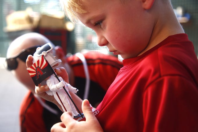 """Mason Tetschner, 5, looks at his Astronaut Nick Ahmed Bobblehead released by the Arizona Diamondbacks outside Chase Field in Phoenix, Ariz. on July 20, 2019, to celebrate the 50th anniversary of the moon landing.&nbsp;<strong>MORE:</strong>&nbsp;<a href=""""https://www.azcentral.com/story/travel/arizona/road-trips/2019/07/01/apollo-11-moon-landing-flagstaff-arizona-meteor-crater-lowell-observatory-cinder-lake-crater-field/1517388001/"""" target=""""_blank"""">Explore AZ&#39;s role in moon landing at these places</a> &nbsp;