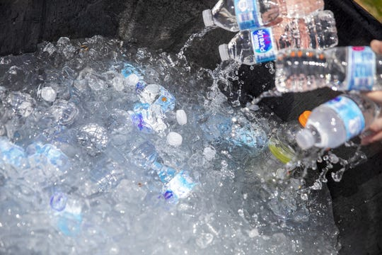Pitchfork volunteers grab water bottles to give to attendees of the music festival during an excessive heat wave in the Chicago area on Saturday, July 20, 2019. (Camille Fine/Chicago Tribune via AP)
