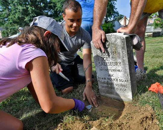 Emily Knight, 9 from Bensalem PA, left, and SGT. Hughes Dejour, a member of the PA Army National Guard C Troop 2nd 104th CAV, uncover a flag marker on a veteran grave at Lebanon Cemetery in North York, Saturday, July 20, 2019. The cemetery, which was the first in York where African-American could be buried, has been in a state of neglect for many years. John A. Pavoncello photo