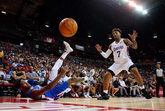 Los Angeles Clippers forward Nigel Hayes passes the ball as he slides on his back against Lakers forward Jordan Caroline during the NBA Summer League at Thomas & Mack Center.