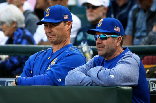 FILE - In this Sept. 10, 2017, file photo, Seattle Mariners manager Scott Servais, left, and hitting coach Edgar Martinez stand at the rail of the dugout during the team's baseball game against the Los Angeles Angels in Seattle. Servais had never crossed paths with Martinez until being hired as Seattle's manager in 2016. Martinez was the hitting coach under the previous regime and remained on staff.
