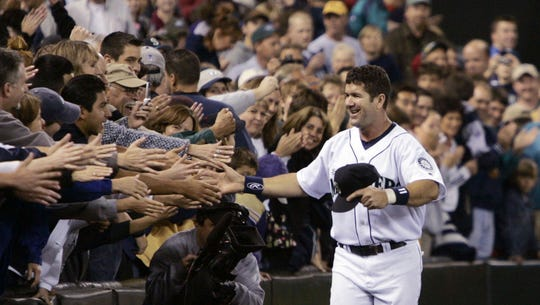 FILE - In this Oct. 2, 2004, file photo, Seattle Mariners' Edgar Martinez is greeted by fans as he jogs a lap around the stadium in Seattle after the team's 10-4 loss to the Texas Rangers in a baseball game on the eve of his final game before retirement. Martinez will go into the Baseball Hall of Fame on Sunday, the first player to spend his entire career with the Mariners--18 seasons in all--and find his way into Cooperstown.