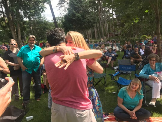 Mark Ristau and Lori Kampa, both of St. Paul, Minn., hug at Munsinger Gardens as a butterfly sits on Kampa's engagement ring.
