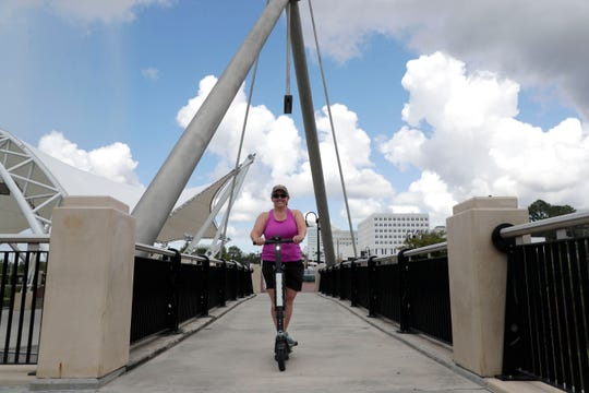 """I love them, I wish there were helmets because they go pretty fast, but they're a neat way to get around,"" said Katie McCormick a second time rider. McCormick rides a scooter across a bridge in Cascades Park Saturday, July 20, 2019."