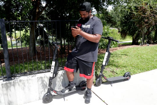 "First time scooter user Sherrod Sutton downloads an app and inputs his information so he can ride through Cascades Park with his son. ""I they're safe, I've seen kids riding them through the neighborhood,"" Sutton said as his son whizzed passed."