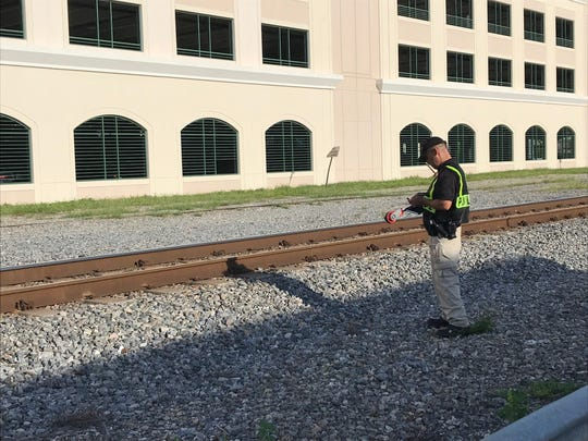 Florida East Coast Railroad Officer Stephen Michael investigates the scene just north of the Orange Avenue railroad crossing in downtown Fort Pierce where a Port St. Lucie man was struck and killed by a train early Sunday, July 21, 2019.