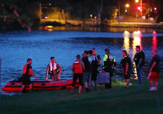 Rescue workers prepare to launch a boat as they search for a missing swimmer in Lake Carmel July 20, 2019.