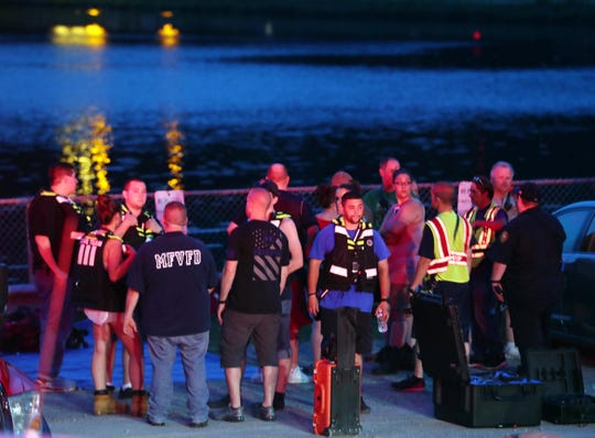 Rescue workers gather on the shores of Lake Carmel as they prepare to search for a missing swimmer July 20, 2019.