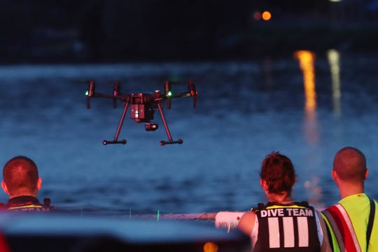 Rescue workers send up a drone as they search for a missing swimmer in Lake Carmel July 20, 2019.