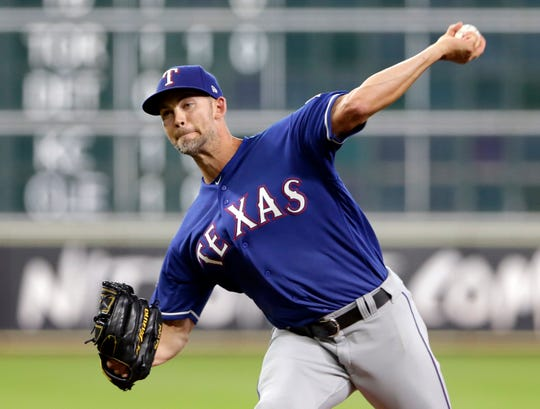 Texas Rangers starting pitcher Mike Minor throws during the first inning of the team's baseball game against the Houston Astros on Friday, July 19, 2019, in Houston. (AP Photo/Michael Wyke)