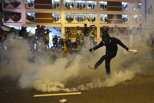 A protester kicks a tear gas canister during confrontation in Hong Kong Sunday, July 21, 2019. Hong Kong police launched tear gas at protesters Sunday after a massive pro-democracy march continued late into the evening. The action was the latest confrontation between police and demonstrators who have taken to the streets to protest an extradition bill and call for electoral reforms in the Chinese territory.