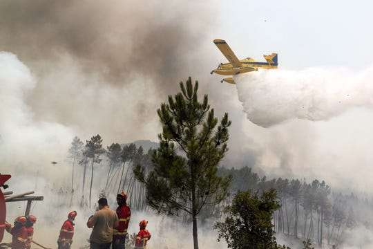 Firefighters and an airplane try to extinguish a wildfire at Sarnadas, near Macao, Portugal, on July 21, 2019.