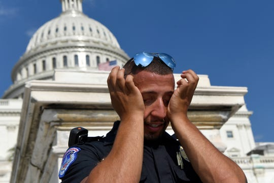 "A Capitol Hill police officer wipes sweat from his eyes as he stands his post on the West side of Capitol Hill in Washington, Saturday, July 20, 2019. The National Weather Service said ""a dangerous heat wave"" was expected to break record highs in some places, particularly for nighttime."
