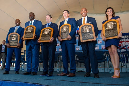 (From left to right) National Baseball Hall of Fame inductees Harold Baines, Lee Smith, Edgar Martinez, Mike Mussina and Mariano Rivera join Brandy Halladay, widow of inductee Roy Halladay, to pose with their Hall of Fame plaques.