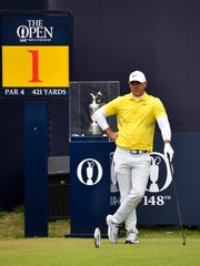 Brooks Koepka stands in front of the Claret Jug on the first tee during the final round of the British Open.
