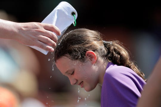A young spectator gets water doused on her by an adult during the seventh inning of a baseball game between the Baltimore Orioles and the Boston Red Sox on July 21, 2019, in Baltimore.