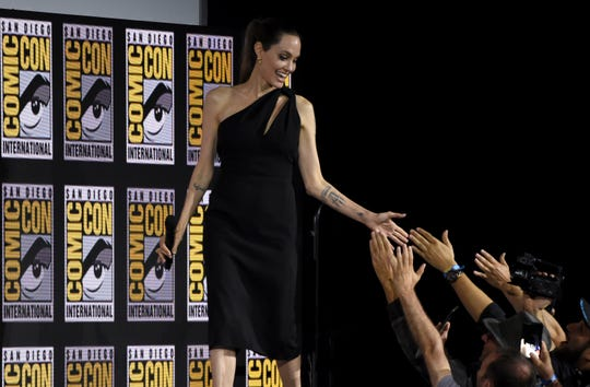 Angelina Jolie hand-slaps fans as she walks out at the Marvel presentation.